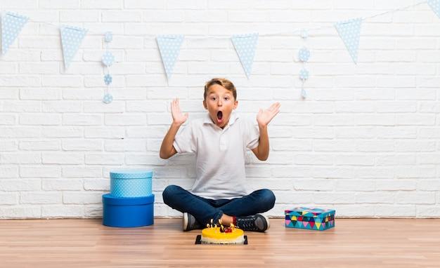 Menino, celebrando, seu, aniversário, com, um, bolo, com, surpresa, e, choque, expressão facial
