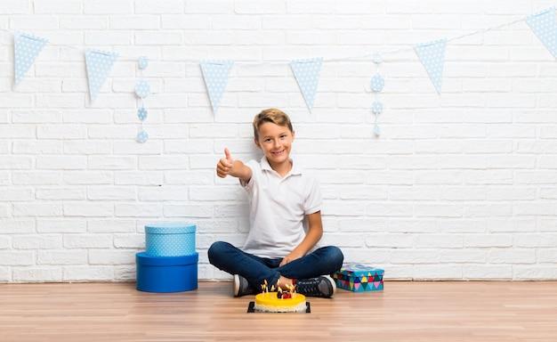 Menino, celebrando, seu, aniversário, com, um, bolo, dar, um, polegares cima, gesto, e, sorrindo