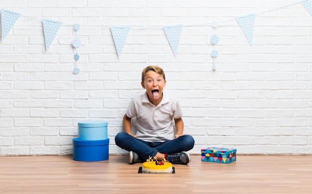 Menino, celebrando, seu, aniversário, com, um, bolo, mostrando, língua, câmera, tendo, engraçado, olhar