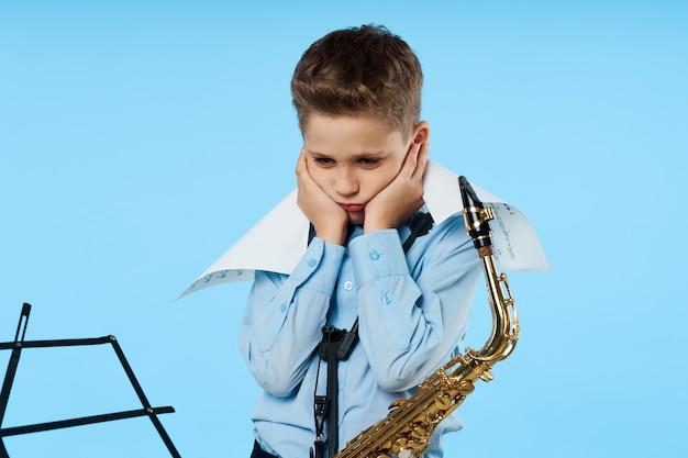 Menino chateado com saxofone olhando para baixo