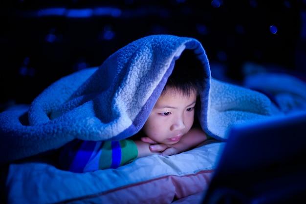 Menino chinês asiático jogando smartphone na cama, garoto usar telefone e jogar jogo, jogo viciado e desenhos animados,