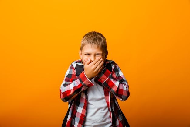 Menino chocado com uma camisa vermelha cobrindo a boca com as mãos em um fundo amarelo