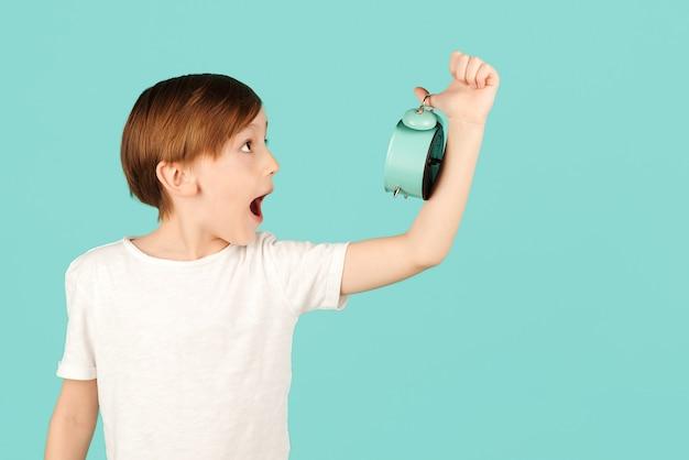 Menino chocado segurando despertador criança com relógio sobre fundo de cor hora da escola