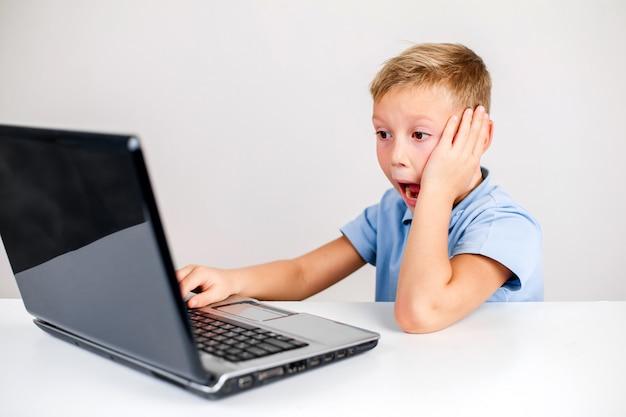 Menino chocado usando laptop com boca aberta
