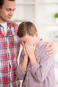 Menino chorando enquanto o pai repreendê-lo.