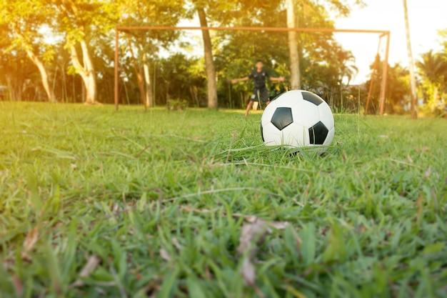 Menino chutando bola de futebol no campo de esportes. fase de treino de futebol para crianças.