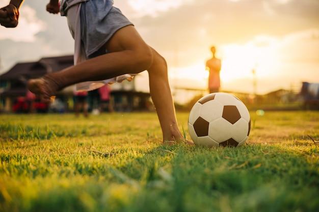 Menino chutando uma bola de futebol com o pé descalço no campo de grama verde