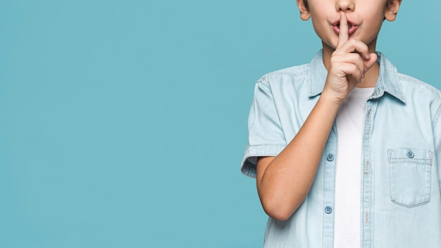 Menino close-up, mostrando, sinal silêncio