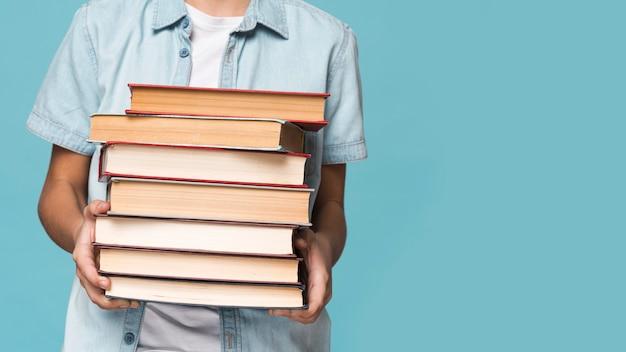 Menino close-up, segurando, pilha livros