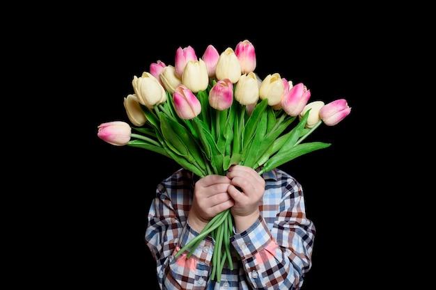 Menino cobre o rosto com um buquê de tulipas. isole em fundo preto.