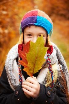 Menino cobrindo o rosto com folhas de outono