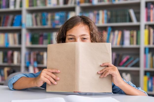 Menino cobrindo o rosto com um livro na biblioteca