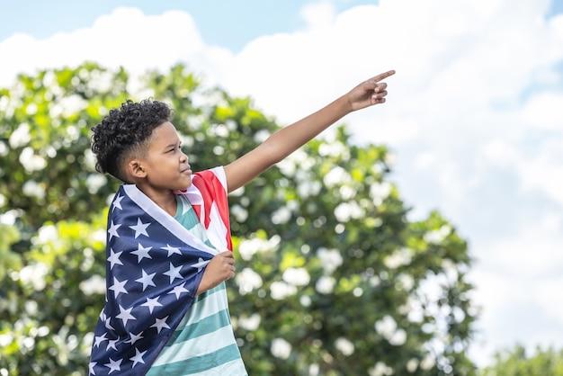 Menino com a bandeira americana dos eua comemorando 4 de julho