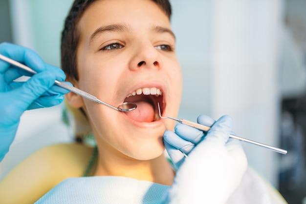 Menino com a boca aberta em um gabinete odontológico