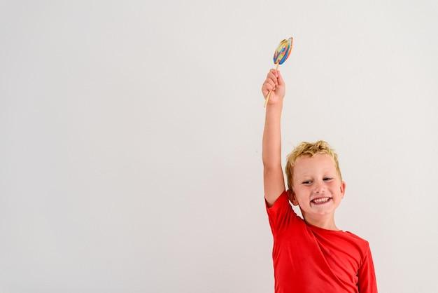 Menino com a camisa vermelha no fundo branco que come um divertimento colorido e um riso do pirulito.