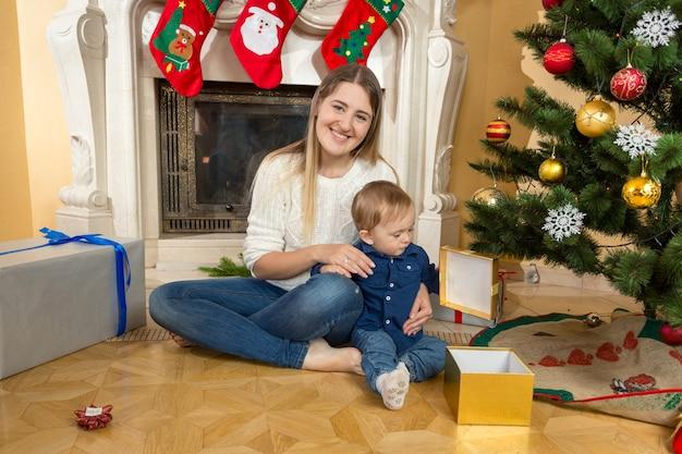 Menino com a mãe abrindo caixas de presente embaixo da árvore de natal na sala de estar