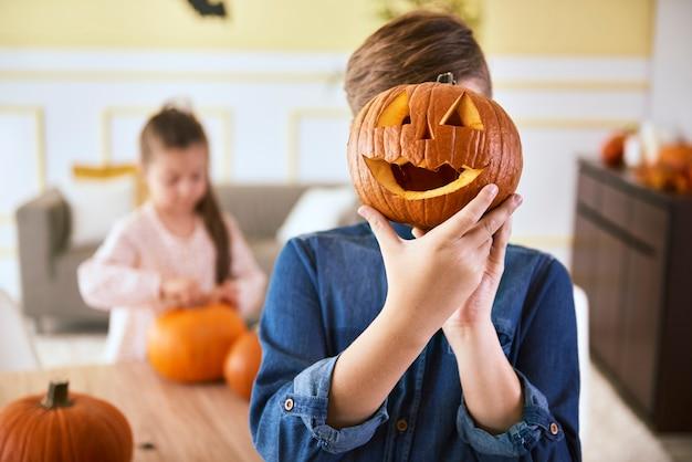 Menino com abóbora de halloween assustadora