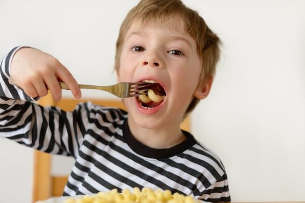 Menino com apetite come macarrão
