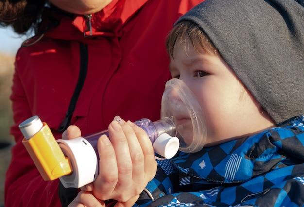 Menino com asma recebendo tratamento com inalador