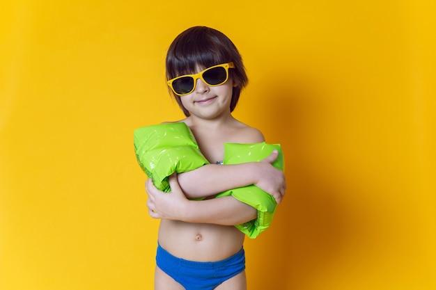 Menino com braçadeiras de natação verdes infláveis e óculos escuros em pé em uma parede amarela