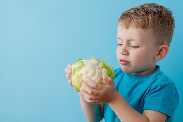 Menino com brócolis nas mãos, dieta e exercícios para o conceito de boa saúde.
