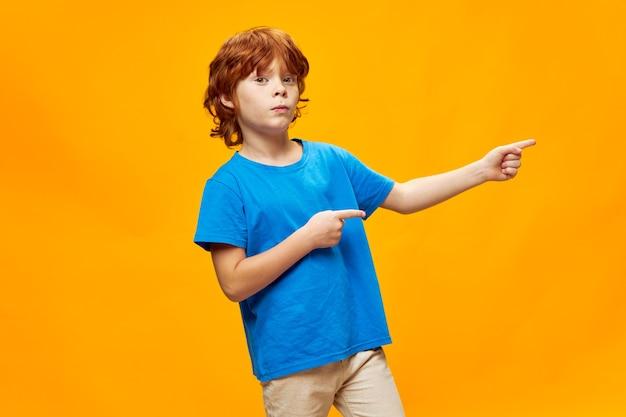 Menino com cabelo ruivo mostra duas mãos com o dedo indicador para o lado da camiseta azul