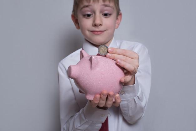 Menino com camisa coloca uma moeda no cofrinho rosa. conceito de negócios. superfície clara