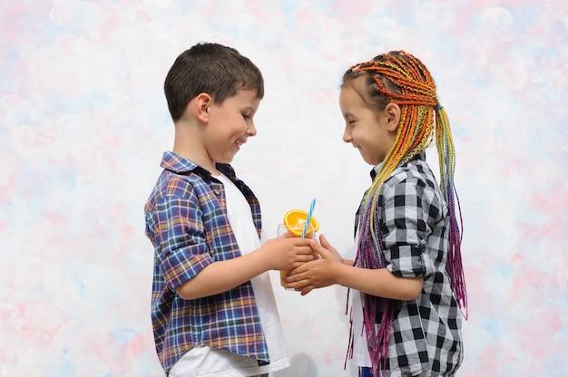 Menino com camisa dando um copo de suco cítrico para uma menina crianças felizes