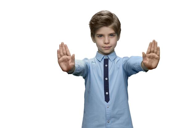 Menino com camiseta azul fazendo gesto de parar com as duas mãos na parede branca