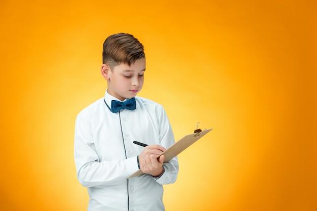 Menino com caneta e prancheta para anotações
