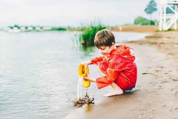 Menino com capa de chuva vermelha despeja água de uma bota de borracha amarela no lago criança brincando com água