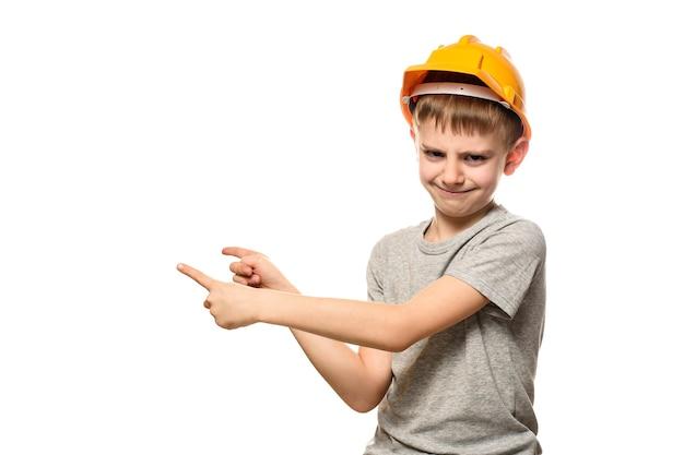 Menino com capacete de construção laranja mostra os indicadores de lado. retrato. isole em fundo branco.
