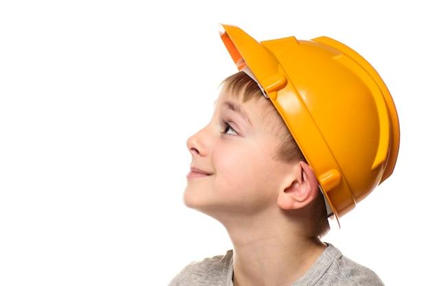 Menino com capacete laranja de construção. retrato, rosto, perfil. isole em fundo branco.