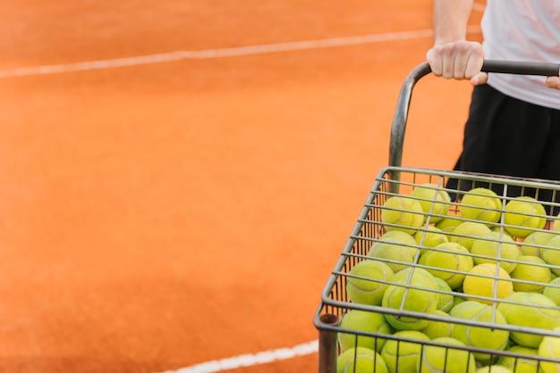 Menino com carrinho de bolas de tênis