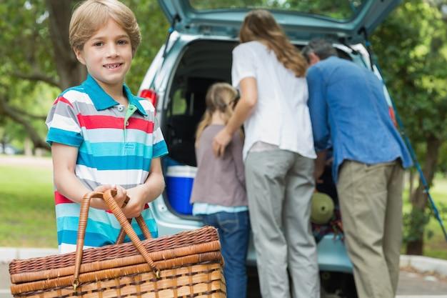 Menino com cesta de piquenique enquanto a família em segundo plano no tronco do carro