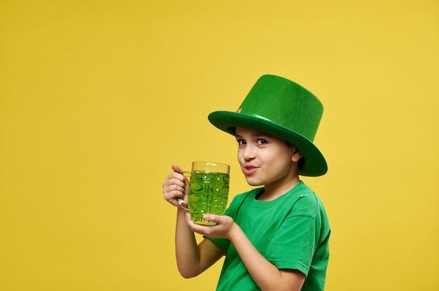 Menino com chapéu de duende bebe bebida verde enquanto olha para a câmera