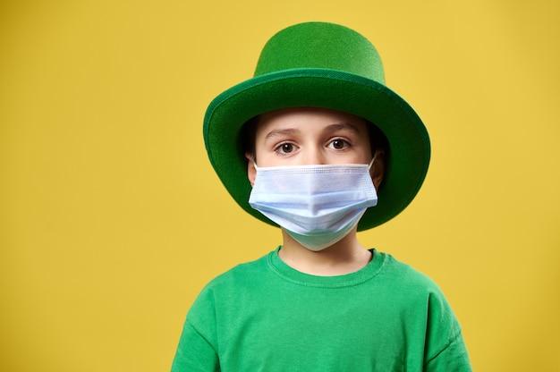 Menino com chapéu de duende irlandês verde e máscara médica protetora posa para a câmera em uma superfície amarela
