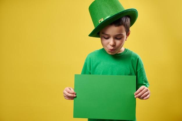 Menino com chapéu de duende verde olhando para uma folha de papel verde nas mãos