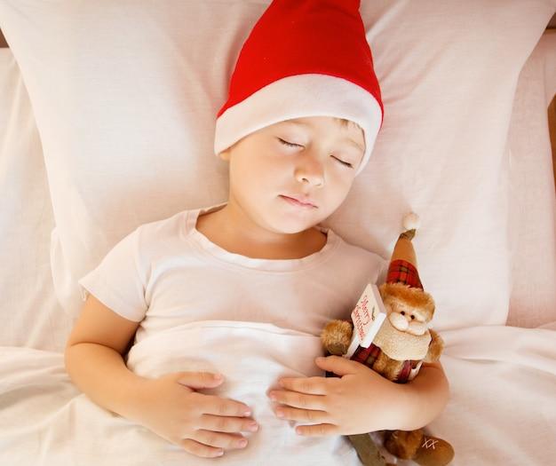 Menino com chapéu de natal com brinquedo de papai noel dormindo na cama