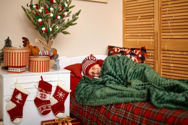 Menino com chapéu de papai noel dormindo ao lado da árvore de natal