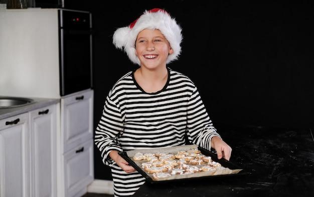 Menino com chapéu de papai noel está fazendo um bolo de natal na cozinha e sorrindo. em tons de preto, vermelho e branco