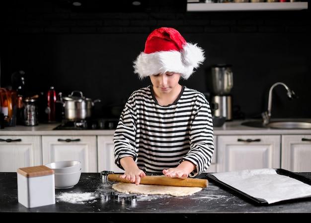 Menino com chapéu de papai noel está fazendo um bolo de natal na cozinha. em tons de preto, vermelho e branco