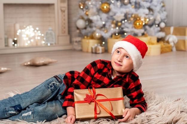 Menino com chapéu de papai noel olhando largo sorrindo. o quarto é decorado com luzes de natal, todas em luzes. elegante árvore de natal coberta de neve em foco. feriado em família o natal agrada a criança