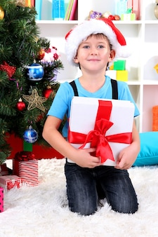 Menino com chapéu de papai noel sentado perto da árvore de natal com um presente nas mãos