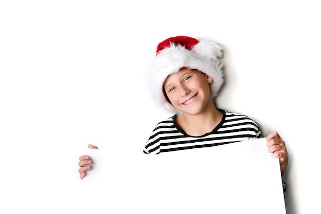 Menino com chapéu de papai noel sorrindo e segurando uma placa branca em branco para saudações. isolado no branco