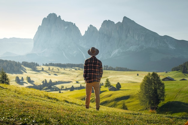 Menino com chapéu e camisa xadrez olhando para o belo vale verde de alpe di siusi, dolomitas