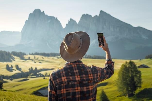Menino com chapéu e camisa xadrez tirando uma selfie nas dolomitas de alpe di siusi