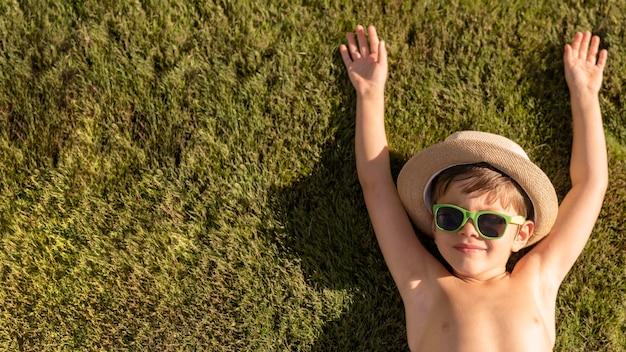 Menino com chapéu e óculos de sol, deitado na grama