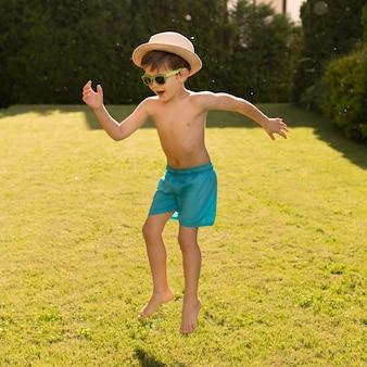 Menino com chapéu e óculos de sol pulando