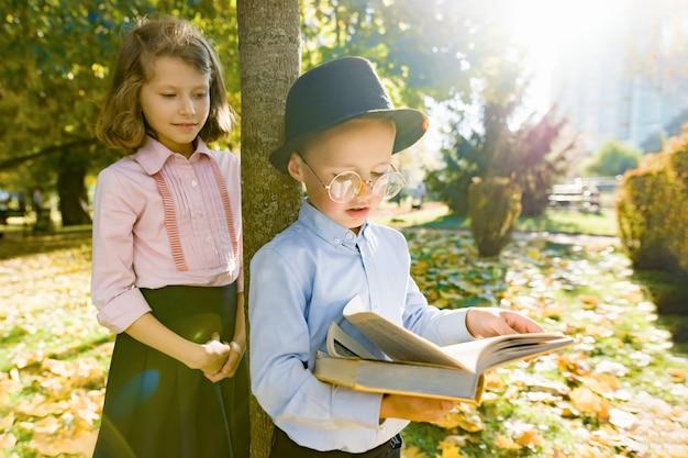 Menino com chapéu, óculos, livro de leitura e menina